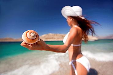 Woman holding a winkle in her hand, Naxos, Cyclades Islands, Greek Islands, Greece, Europe.
