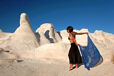Woman posing near the white rock forms in Sarakiniko beach, Milos, Cyclades Islands, Greek Islands, Greece, Europe.