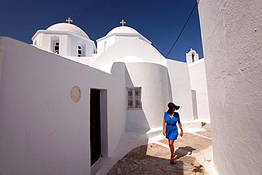 Woman walking through the alley in Chora with the church in the background, Amorgos, Cyclades Islands, Greek Islands, Greece, Europe.