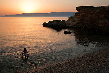 Woman in bikini going to have a swim, Koufonissi, Cyclades Islands, Greek Islands, Greece, Europe.