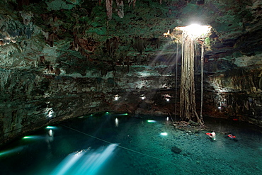 Tourists enjoying a swim in Cenote Samula, Valladolid, Yucatan province, Mexico.