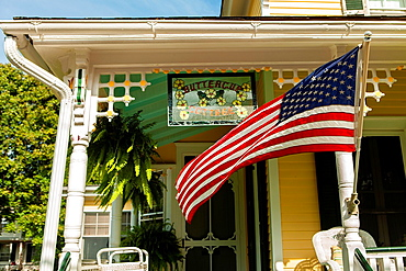 Cape May is America¥s first seaside resort. It has the largest collection of Victorian Architecture in the United States. A white victorian trim and an american flag and a front porch is distinctly a nostalgic image of early 20th Century small town America