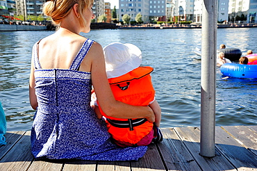 Mother and child with life jacket sitting on a dock, Stockholm, Sweden