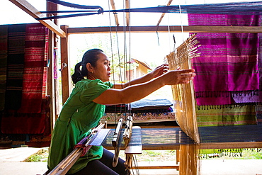 Lao woman making traditional fabric on her loom near Vang Vieng, Laos.