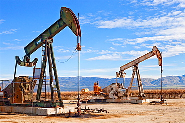 Oil well with pump and grape vines in distance at Kern Co. California.