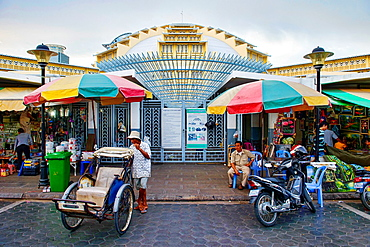 cyclos at the entrance to the Art Deco Psar Thmei Central Market, Phnom Penh, Cambodia.
