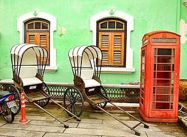 trishaws and phone booth at the Pinang Peranakan Mansion in Georgetown, Penang, Malaysia.