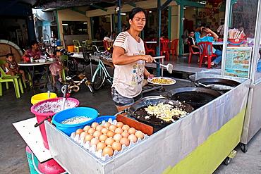 Vendor selling fried oyster pancake at Kampung Pulau Ketam Crab Island fishing village, Malaysia.