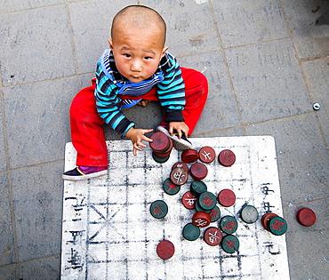 A cute Chinese boy playing Chinese chess.