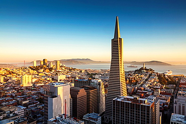 San Francisco skyline and Transamerica Pyramid with Golden Gate Bridge in the background at sunrise, California, USA