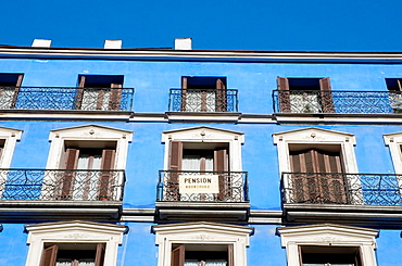 Blue facade of house, Mayor street. Madrid, Spain.