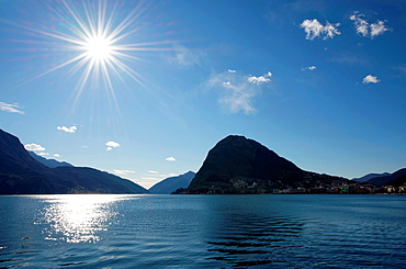 Alpine lake lugano with sun and mountain in lugano ticino switzerland.
