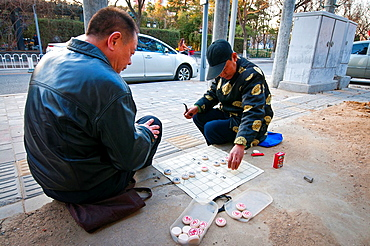 Two men playing Xiangqi also called Chinese chess on the street in Beijing, China.