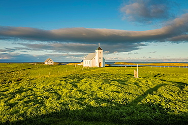 Grasslands and Flatey Church, Flatey Island, Borgarfjordur, Iceland.
