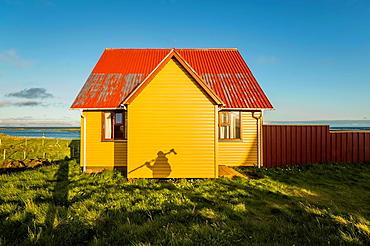 Shadow of photographer with tripod on Summer house, Flatey Island, Borgarfjordur, Iceland.