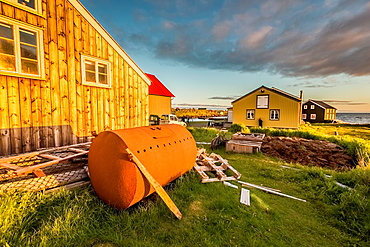 Old rusting oil tank and summer houses, Flatey Island, Iceland.