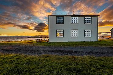 Midnight sun over house on Flatey Island, Borgarfjordur, Iceland.