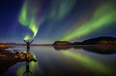 Woman enjoying the view of the Northern Lights, at Lake Thingvellir, Iceland. Thingvellir National Park is a UNESCO World Heritage Site.