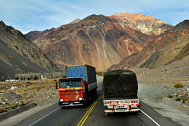 Two heavy trucks, going in opposite direction, pas each other in the high Andes near the border of Chile and Argentina.