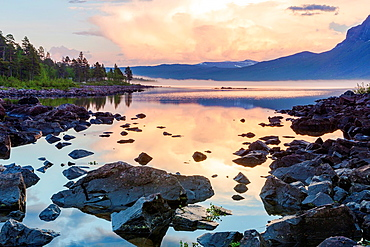 Dawn at stora sjofallets national park with sun reflecting in the water and mountains in the background in Gallivare swedish lapland, Sweden.