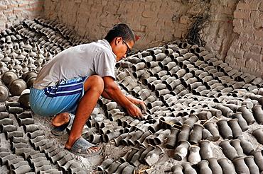 Preparing for firing of pottery, Bhaktapur, Nepal