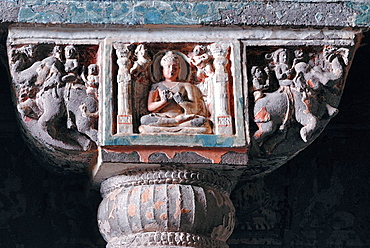 Cave 19 : Pillar capital. Central portion shows Buddha. Either side are two dwarf figures with garlands. Ajanta Caves, Aurangabad, India.