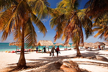 Tourists, parasols and thatched umbrellas on the beach of Playa Ancon near Trinidad, Sancti Spiritus, Cuba, West Indies, Central America.