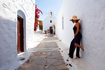 Woman posing in front of a wall, Amorgos, Cyclades Islands, Greek Islands, Greece, Europe.