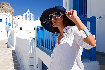 Woman posing in Chora near a church, Amorgos, Cyclades Islands, Greek Islands, Greece, Europe.