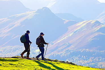 Hikers walking on Latrigg with Cat Bells behind Lake District National Park Cumbria England United Kingdom Great Britain.