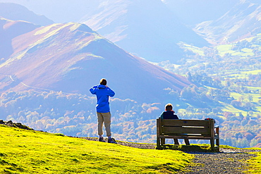 Tourists standing and sitting on a bench, enjoying the view of Cat Bells in the Lake District National Park Cumbria England United Kingdom Great Britain.