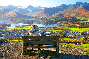 Female walkers sitting on a bench looking at the view above Derwentwater in the Lake District National Park with the Northern Fells in background.