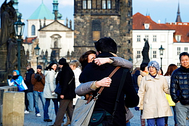 A couple kising pasionately on the Charles Bridge.