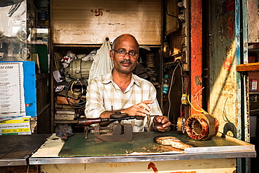 A man sits behind the counter in his shop repairing small electrical equipment.