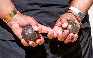 Two metal balls for game in petanque in man's hands.
