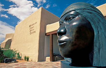 A sculpture of a Native North American stands in front of Santa Fe's Museum of Indian Arts and Culture in New Mexico