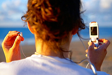 16 years old teenager listening to music in a MP3 mobile phone, Hendaye beach, Aquitaine, France.