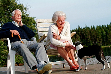94 year old man with wife and dog enjoying sunset on dock, Medevi, Sweden