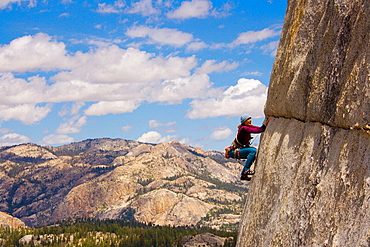 Climbing 'On The Lamb', rated 5.10,  This crack splits The Lamb dome horizontally creating a perfect path for climbers, Summer thunderheads are building in the distant High Sierra, USA.