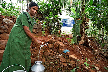 Woman collecting safe drinking water, Kerala, India