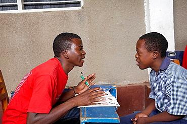 Godfrey Anthony (left) teaching 13-year-old developmemntally disabled Agostino in Huruma school for handicapped children, Mwanza, Tanzania