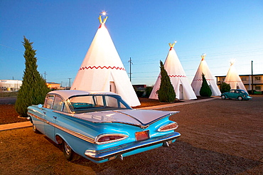 Wigwam motel concrete teepees and 1959 Chevrolet on Route 66 at evening, Holbrook, Arizona, USA