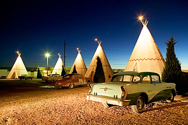 Wigwam motel concrete teepees and 1954 Buick on Route 66 at evening, Holbrook, Arizona, USA