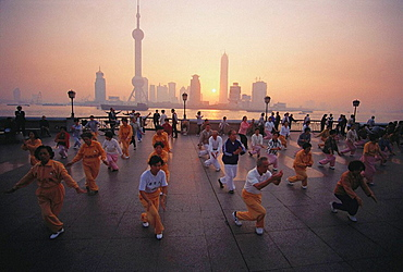 Morning exercises on the Bund with Pudong skyline across Huangpu river, Shanghai, China