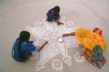 Three women painting a mandana (colourful floor design) in Rajasthan, India