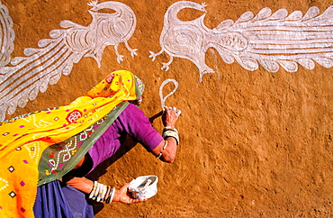 Woman decorating a wall with paintings, Region of Tonk, Rajasthan, India