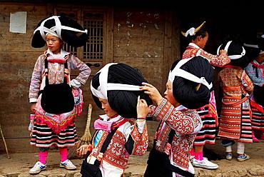 China, Guizhou province, Longjia village, Long Horn Miao girls in traditional costumes celebrating Flower Dance Festival.