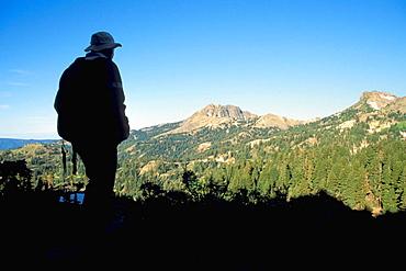 Hiker on trail to Bumpass Hell overlooking Brokeoff Mountain and Mount Diller peak, Lassen Volcanic National Park, California