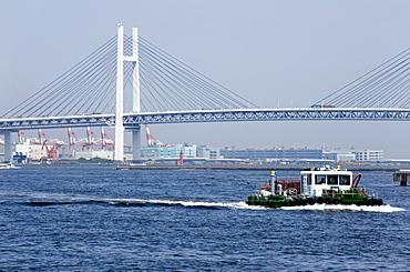 Tug boat passing by the Yokohama Bay Bridge which spans the Tokyo Bay in Yokohama, Japan, Asia