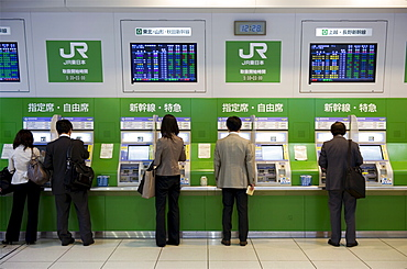Passengers purchasing bullet train tickets from vending machines at the central JR (Japan Railway) station in Tokyo, Japan, Asia